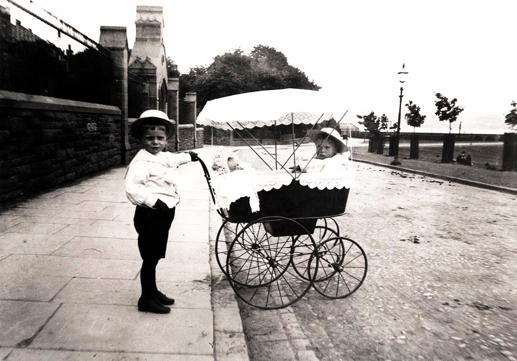 Small Boy Pushing Pram with Baby and Child in It